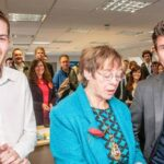 three people in the foreground whilst a full office stands behind, everyone smiling for photo - virtual team