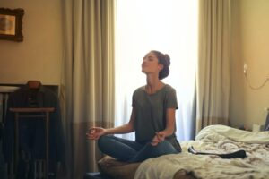 Woman meditating on her bed managing work-life balance
