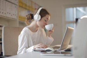 Woman in white shirt on laptop drinking coffee while listening to music on her laptop
