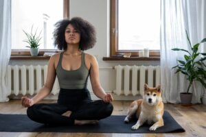 Women sitting on yoga mat meditating with her dog