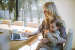 Blonde woman with baby on her lap working on her laptop