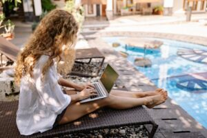 self-employed woman sitting on her laptop at a pool taking a sabbatical