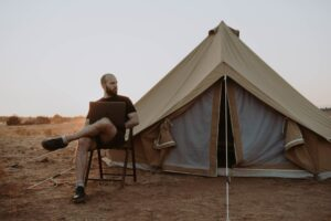 Man on his laptop taking a sabbatical sitting outside his tent in the desert