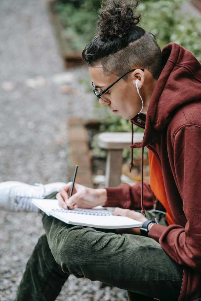 Man in red pullover and green pants listening to music while writing in a book