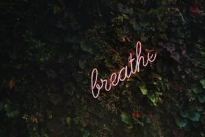 "Neon sign on a wall reading ""breathe"""