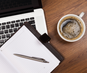 A diary, laptop and cup of coffee on a desk making a list of how to hire the right assistant..