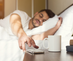 Man in bed hitting snooze button on his cellphone alarm