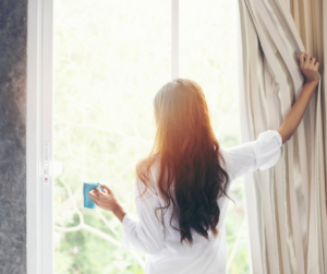 Woman waking up early looking out the window drinking coffee for a productive morning routine