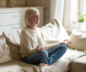 Woman sitting on a white couch meditating