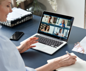 A woman sitting at her laptop having a meeting with her virtual team