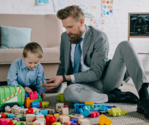 A man is a suit playing with his son and his toys