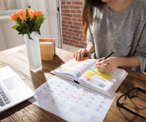 Woman sitting at her desk scheduling her day to reduce stress