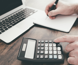 Man on calculator working out monthly finances