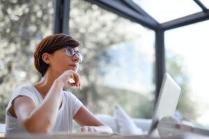 Woman daydreaming at laptop