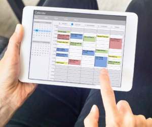 A person on their tablet organising their monthly calendar