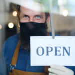 Man in a mask with a open sign in the window of his shop