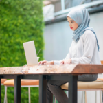 A female virtual assistant sitting at a table looking at her laptop