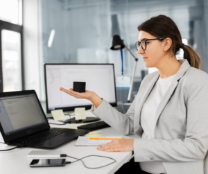 A female virtual assistant in a grey jacket sitting at her desk