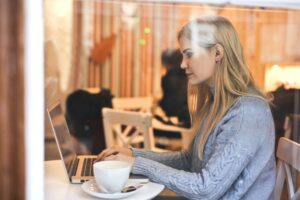 A virtual assistant wearing a grey top sitting at her laptop in a coffee shop drinking coffee