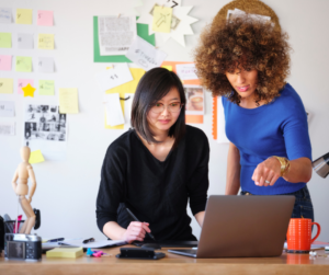 Two women looking at a laptop learning how to delegate and why you need a personal assistant