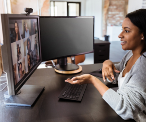 A woman sitting at her desk having a video meeting as a way to manage a virtual team