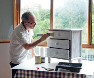 A man painting a chest of drawers
