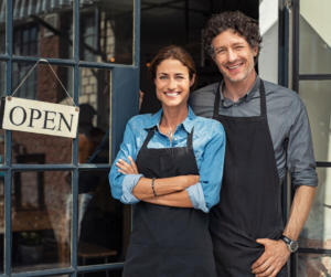 """A man and a woman standing in front of a shop with a """"open"""" sign in the wind"""