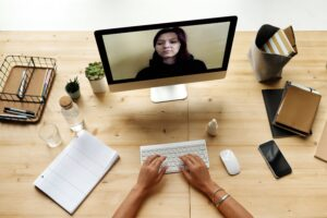 A person sitting at a desk having a video call with a remote team member