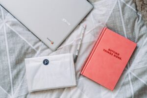 A diary and laptop on a bed showing how to be less busy