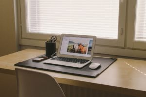 An organised workspace with a laptop on a desk to avoid any common time-wasting traps