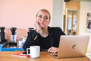 A blonde woman sitting at her desk with coffee and a laptop looking bored