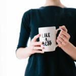 "A woman holding a mug with ""like a boss"" printed on it"
