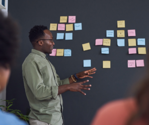 A man standing in front of a team talking about the sticky notes on a board