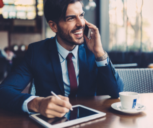 A happy businessman sitting in a coffee shop talking on the phone