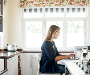 A woman sitting at her kitchen counter working on her laptop